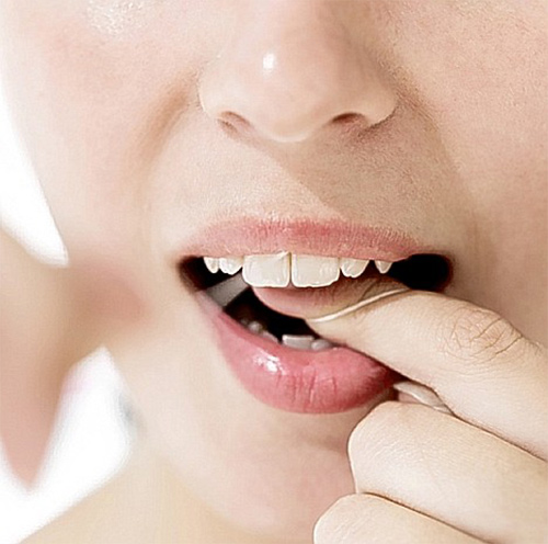 close-up of a woman flossing